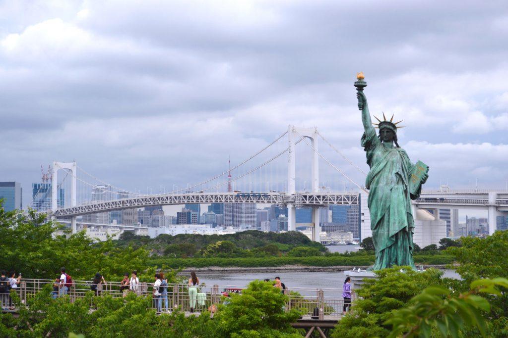 La statut de la liberté d'Odaiba, à l'arrière le Rainbow Bridge et la ville de Tokyo