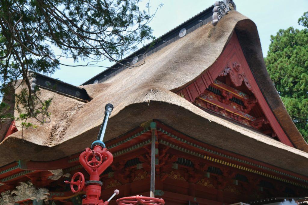 Une lance à incendie pour contrer un feu du toit de chaume du temple