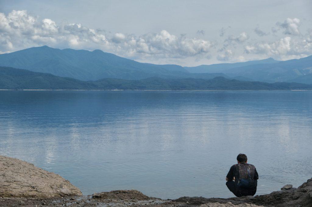Un homme contemple les eaux du lac Tazawa