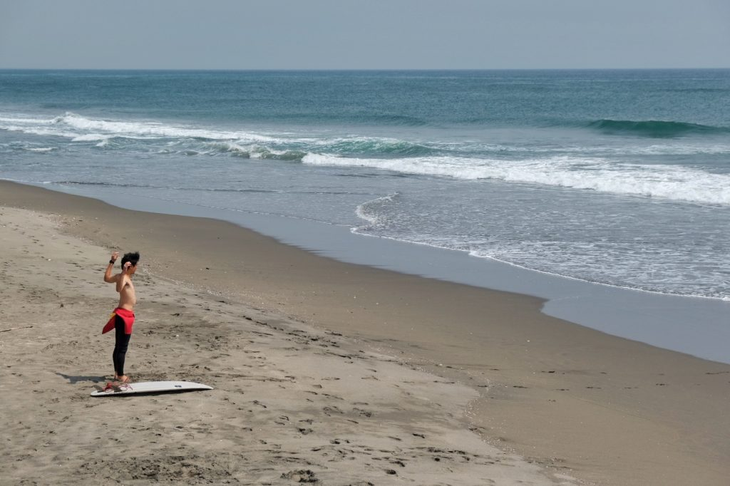 Un surfeur se prépare à braver l'océan Pacifique
