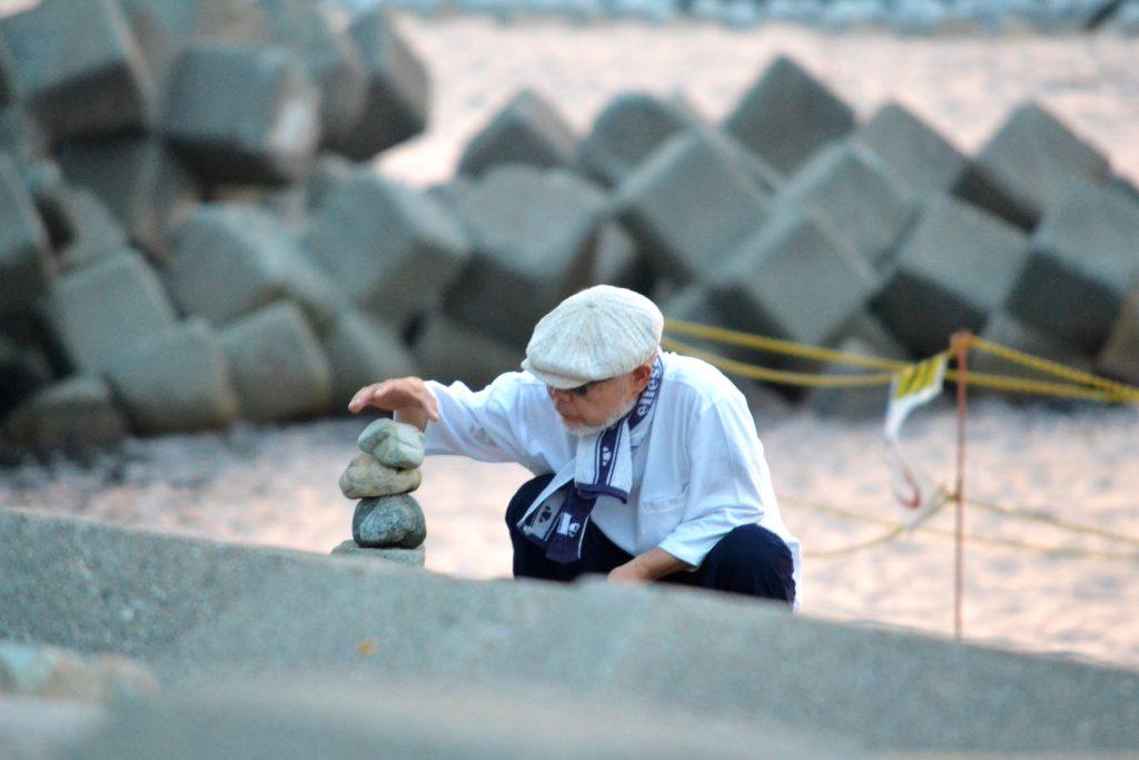 Un homme met des pierres en équilibre