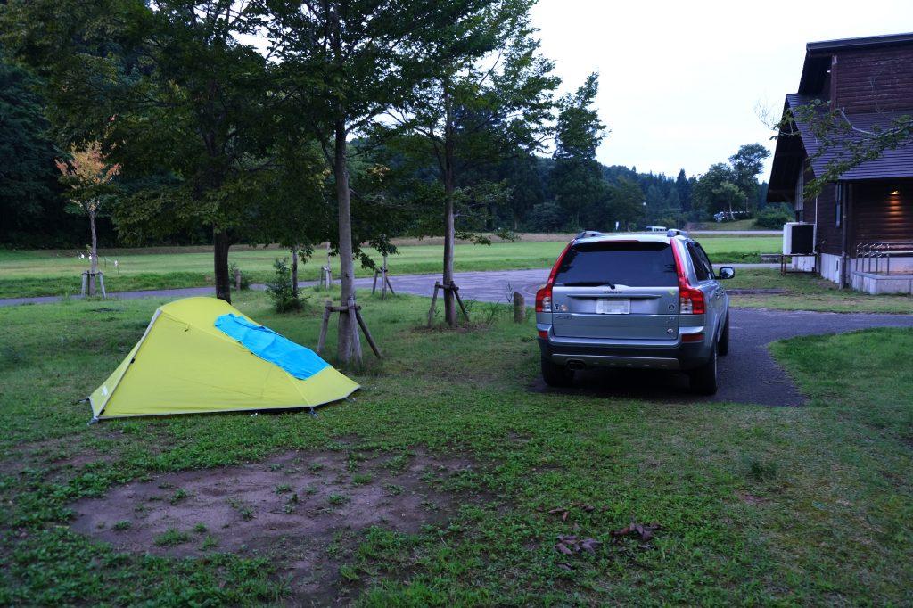 Un camping payant avec place pour la voiture à côté de la tente