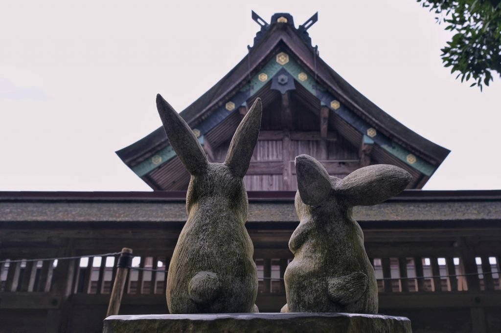 Petite sculpture de lapins contemplant le haut du Izumo Taisha