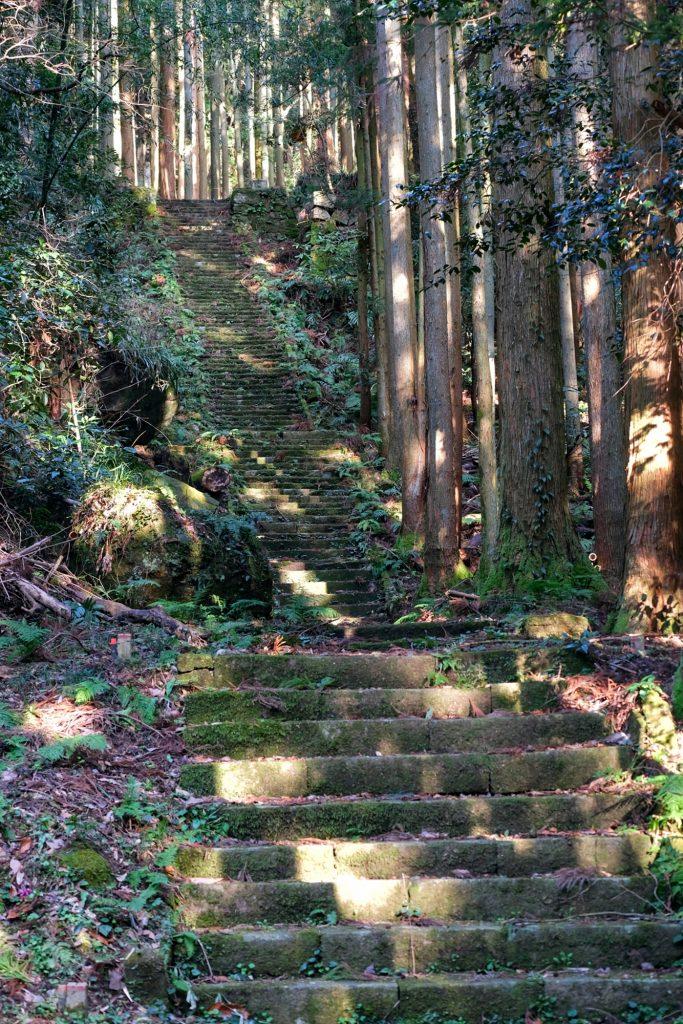 Des escaliers menant vers des ruines d'un temple dans la vallée d'Iwami Ginzan
