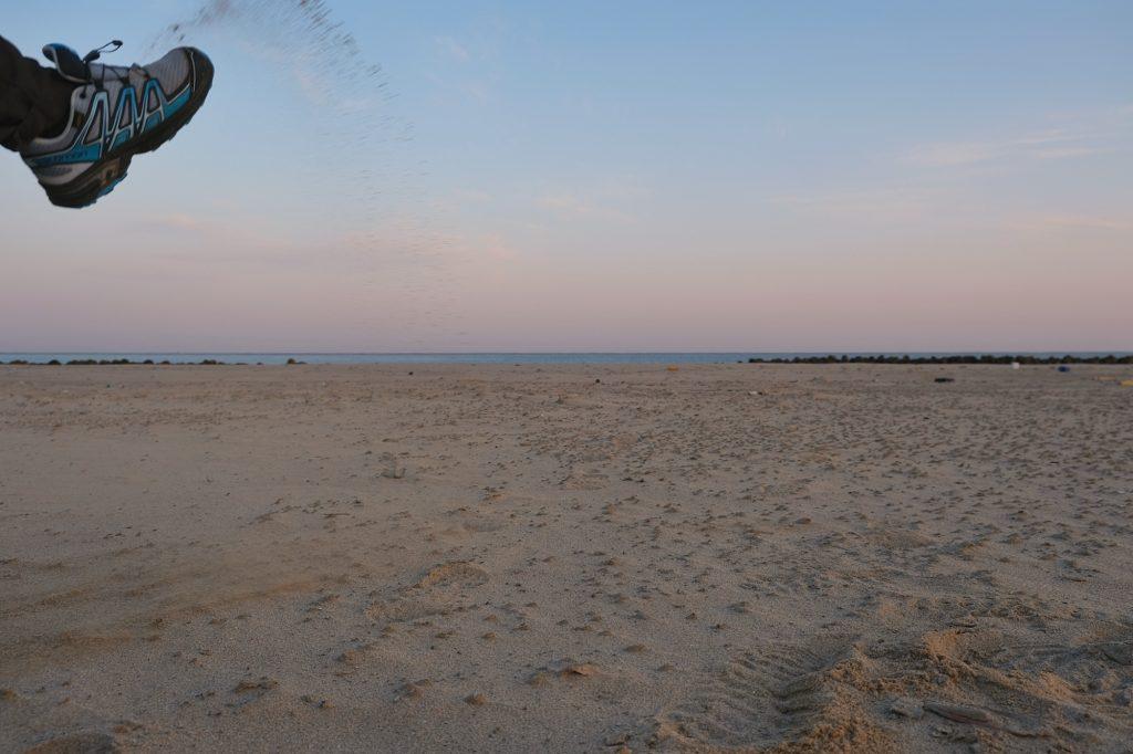 Un pied jette du sable devant l'objectif