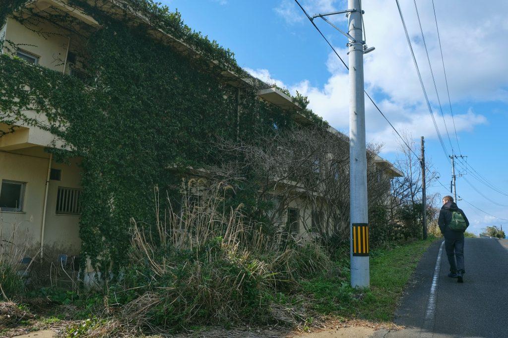 Vincent passe à côté d'un petit immeuble abandonnée d'Ikeshima
