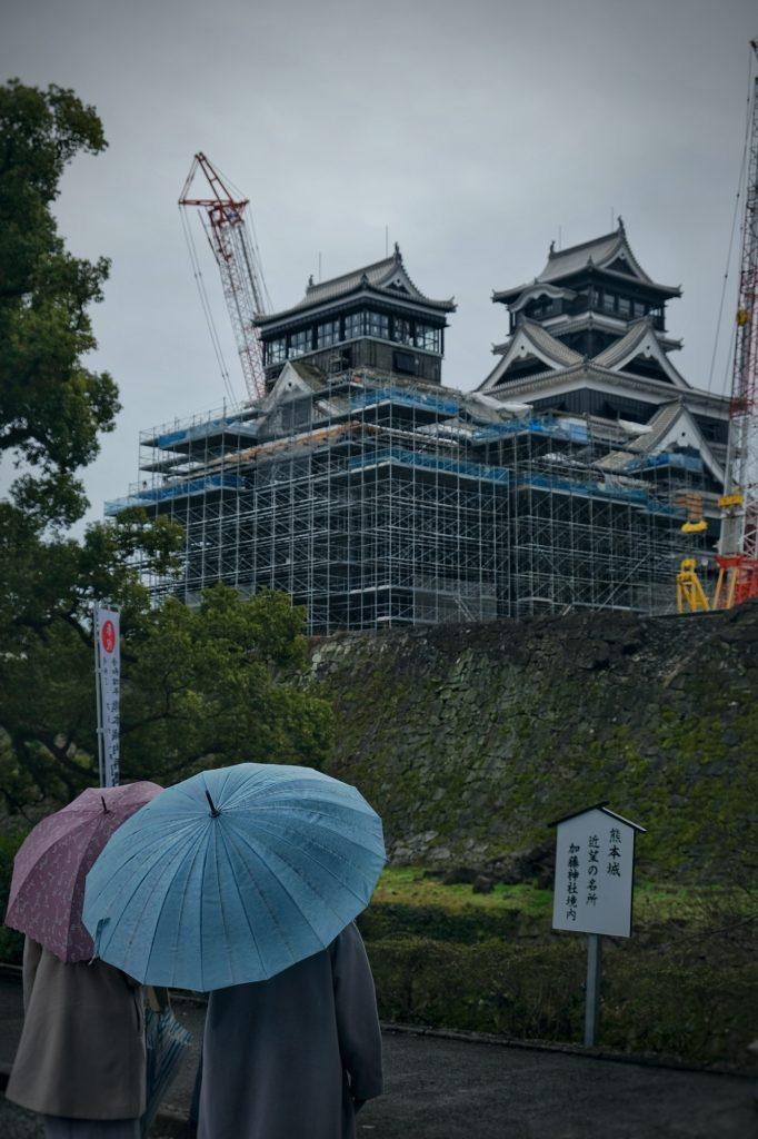 Les visiteurs contemplent (de loin) le château de Kumamoto en reconstruction suite au tremblement de terre de 2016