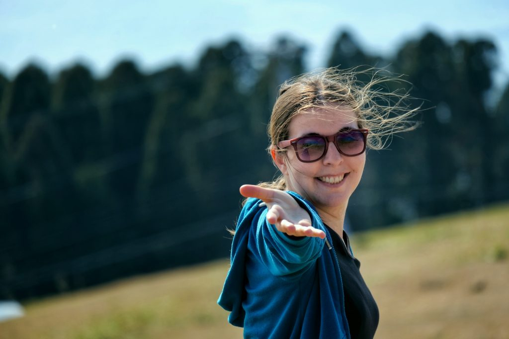Claire, cheveux au vent et main tendue vers moi, au cap Toi