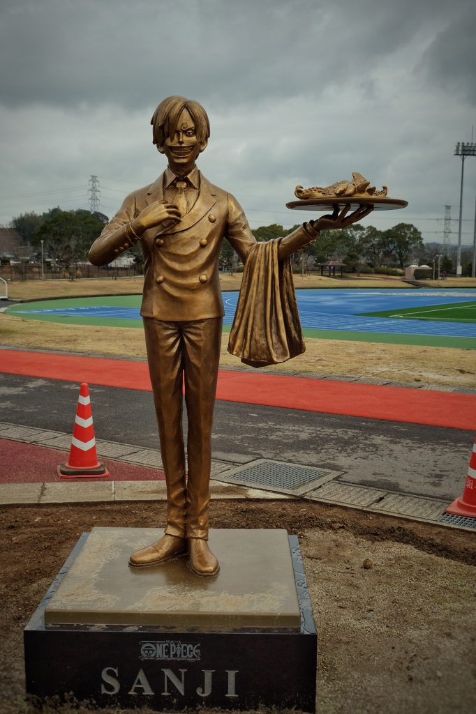 Sanji se trouve près d'un terrain de sport en périphérie de Kumamoto