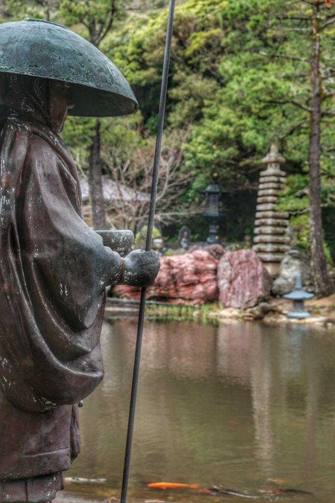 Statue de pèlerin au bord de l'étang du Kongofukuji