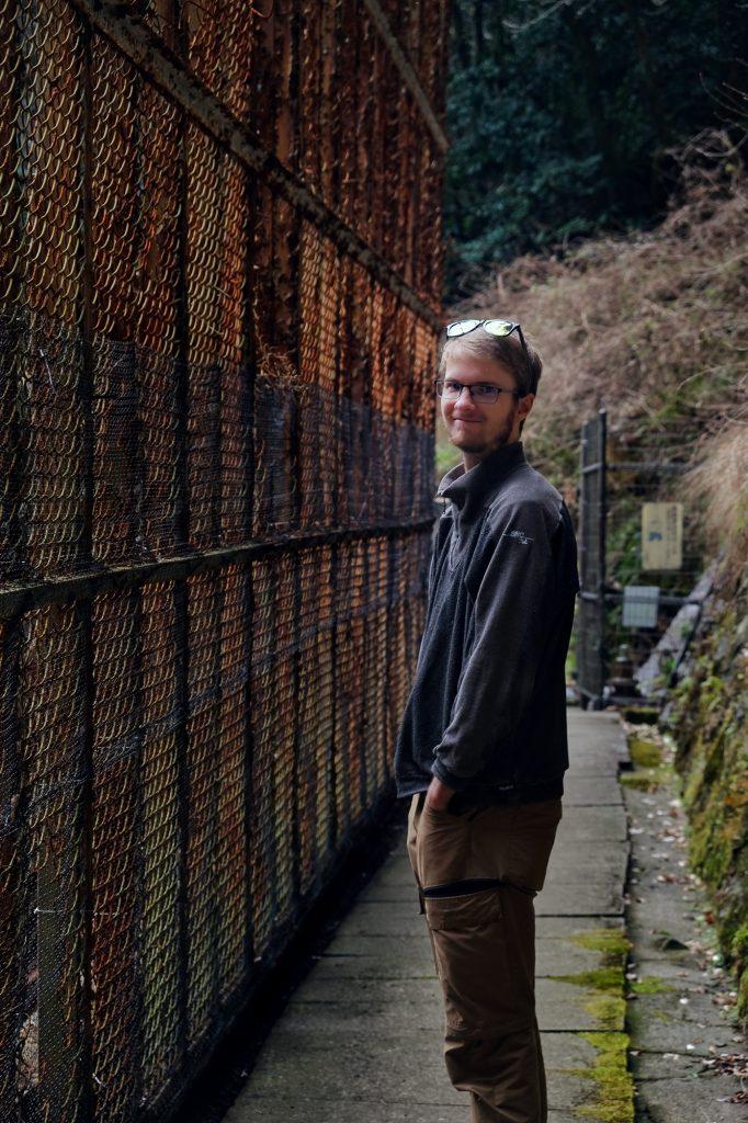 Vincent devant les installations rouillées de la cascade de Sengaki