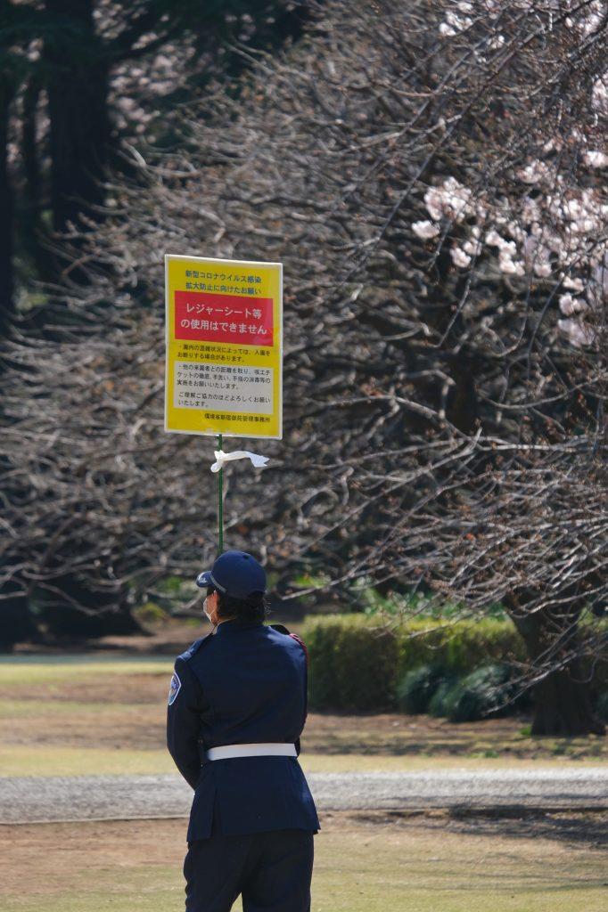 Surveillant pour empêcher les gens de se poser sur les pelouses du Shinjuku Gyoen